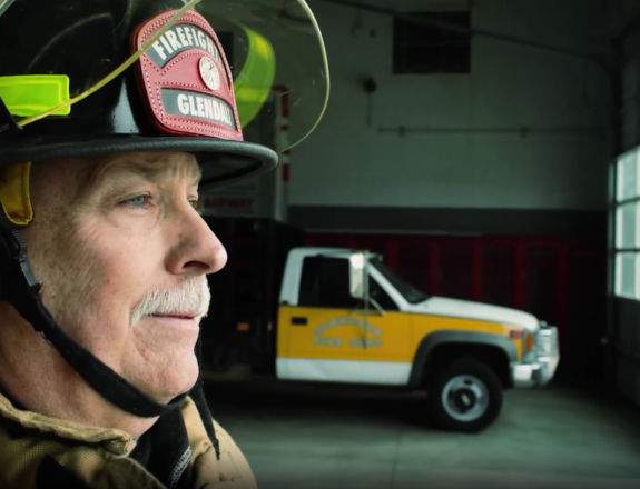 A firefighter and a car in background